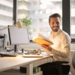 Mann mit Buch am Schreibtisch